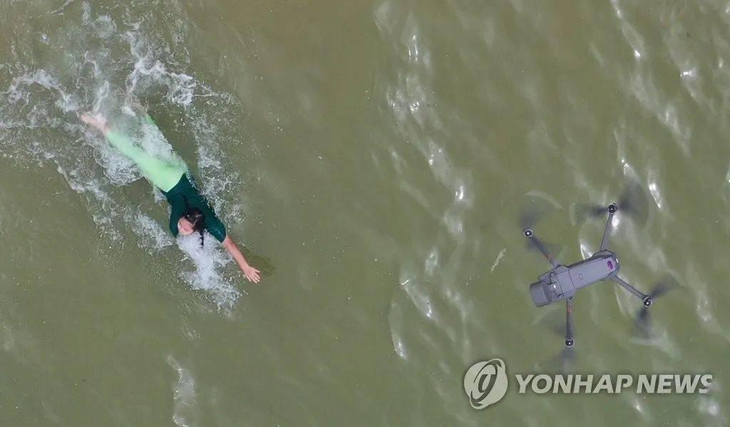 利用无人机,对沙滩上的访客进行测温。
